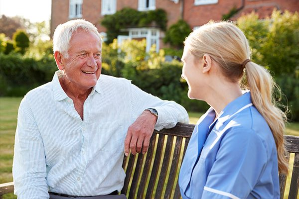 An image of an elderly man with dementia talking to a nurse